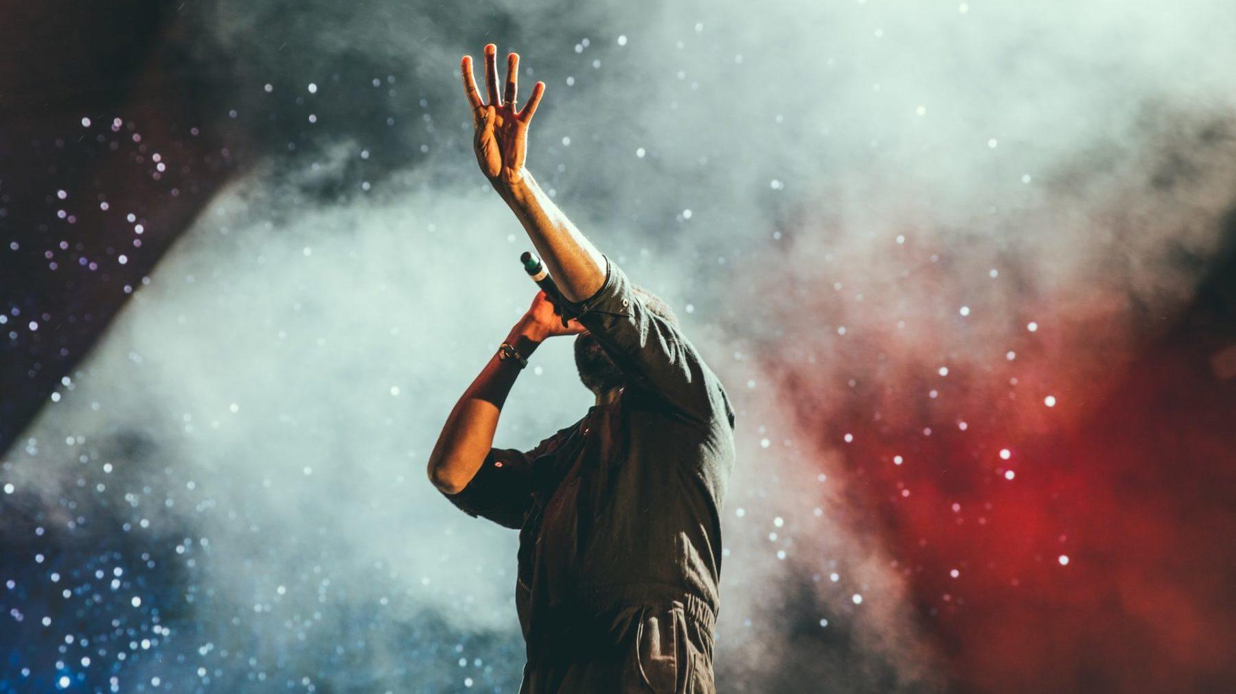 sanger på scenen, med mikrofon, farger og røyk i bakgrunnen