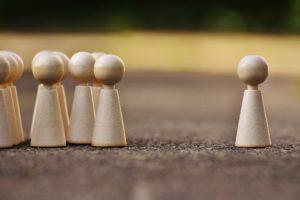 Brikker Som Symboliserer Mennesker - Plassert En Alene Og Resten I En Gruppe