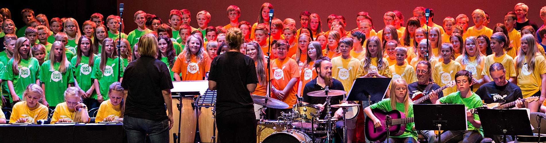 Mange Barn På Scenen Under Konsert, - Fargede T-skjorter - Voksne Og Barn Akkompagnerer