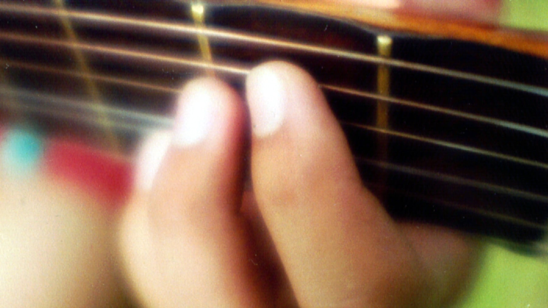 Nærbilde av fingre på gitarhals